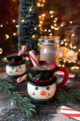 Hot chocolate in smiling snowman mugs in Christmas setting closeup