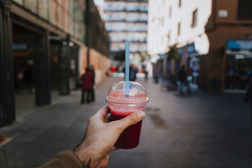 Hand holding a smoothie with red color. Urban city background