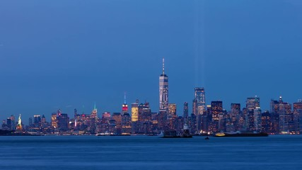 Wall Mural - Timelapse of Lower Manhattan at dusk with the two beams of lights from the Tribute in Light coming on. New York City Harbor