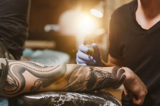 Close up of professional tattooer artist doing picture on hand of man by machine black ink from a jar. Tattoo art on body. Equipment for making tattoo art. Master makes tattooed in light studio.