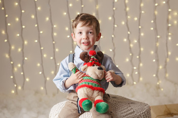 Portrait of white Caucasian boy holding deer moose toy celebrating Christmas or New Year. Little adorable cute child in studio with winter holiday decoration