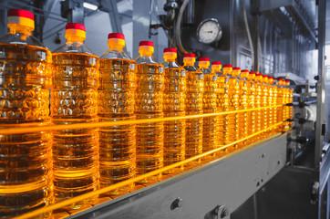 Oil in bottles. Industrial production of sunflower oil. Conveyor line for bottling and packing. Sunflower oil plant.