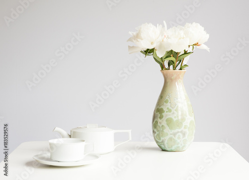 White Peonies In Green Vase On Table With Cup And Saucer And Teapot
