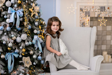 Merry Christmas celebration. Beautiful little girl in a amazing dress near the Christmas tree. Christmas miracles. Happy New Year
