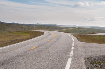 The road is far away against the background of stony hills