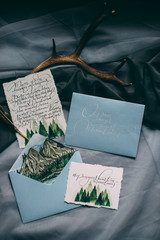 A winter themed greeting card mock up with gold envelope and ornaments.