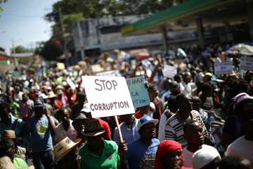 Protesters walk along a street during a march to protest against corruption in Port-au-Prince