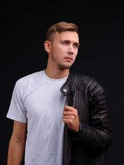 A guy in a T-shirt and half dressed in a leather jacket and looks away with a piercing gaze.