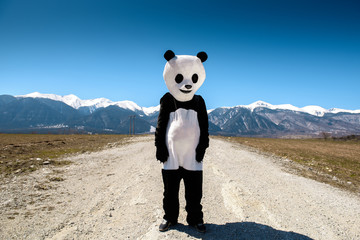A man in a panda suit is waiting on an empty road against a background of mountains. Bulgaria, Bansko - 2015.