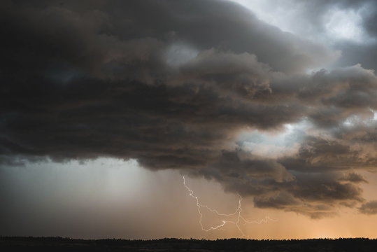 Scenic view of thunderstorm clouds over landscape