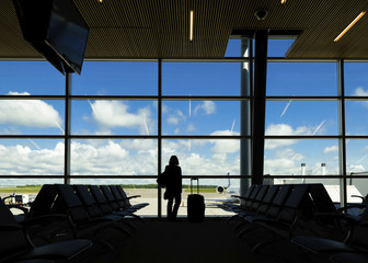 Silhouette woman with suitcase standing against window at airport