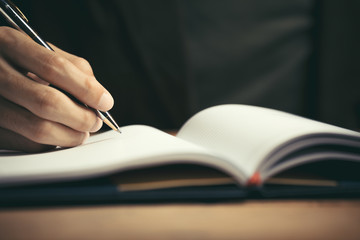 Male hand with pen writing in notebook on desktop