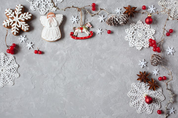 Christmas background with twigs, cones, red berries, angel, lacy snowflakes, gingerbreads