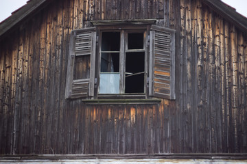 View of the old log hut with a porch and a window