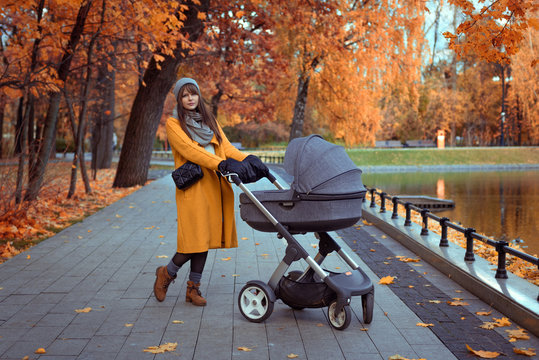 young girl in an autumn park with a baby stroller in moscow, russia