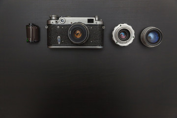 Vintage Film Camera And Accessories On Black Wooden Background Technology Development Concept with copy space. Top View
