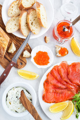 Delicious lunch with salted salmon, red caviar, fresh bread and cream cheese