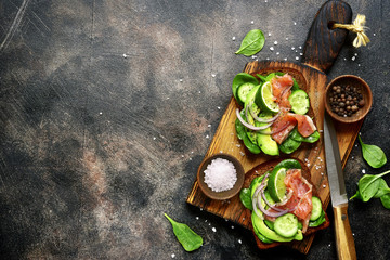Rye toasts with avocado,cucumber,salmon,and spinach.Top view with copy space.