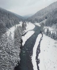 Winter landscape from air. Forest and river in the winter mountain valley