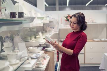 female customer choosing utensil dishes in the supermarket mall.