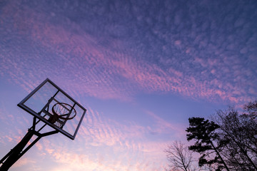 Silhouette of outdoor basketball goal with clear backboard and sunset in the background