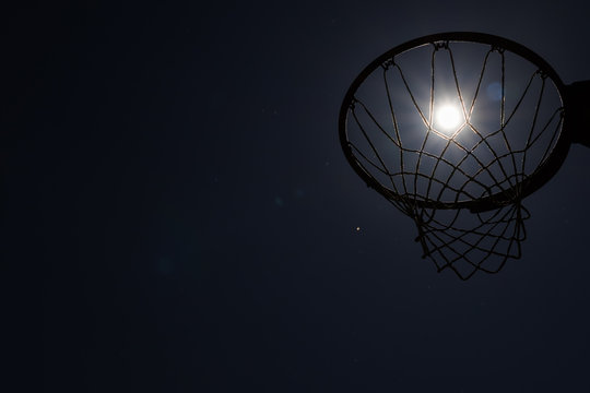 Looking up through silhouetted basketball goal to the moon at night