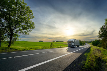 Fotobehang - White truck driving on the asphalt road next to the green field in rural landscape at sunset