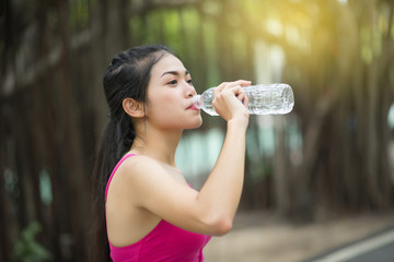 The girl is drinking water after exercising in the morning.