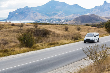 minivan is moving on a country road in a mountainous area