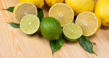 on wooden boards are spread lemons and lime for the background, with green branches