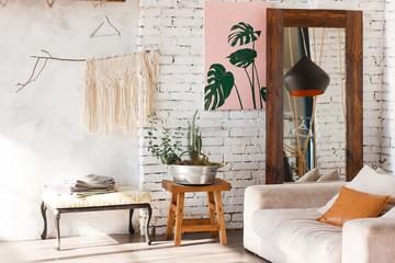 Bright loft interior with white brick walls, mirror, modern light, sofa, decor.