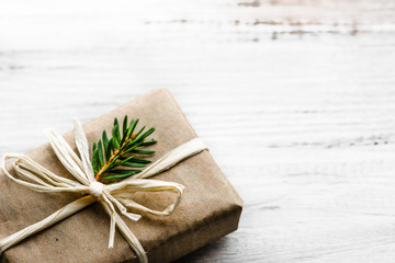 Christmas gift box, present in rustic package with green fir branch on white background