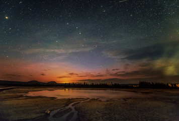 The summer night at Yellowstone National Park, Wyoming. Midway Geyser Basin against the background of the night sky and constellation Big Dipper (selective focus on the stars)