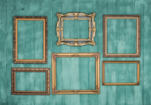 gallery of vintage victorian golden frames isolated on green wooden wall, framework