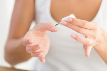 woman painting nails at home