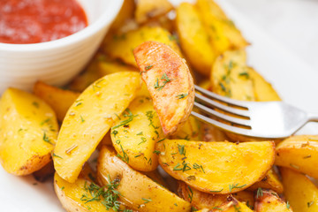 Baked potato slices with herbs in a white dish