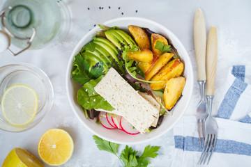 Buddha bowl salad with tofu, baked potatoes, avocado. Top view