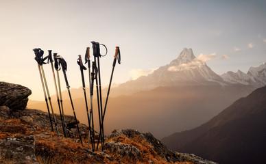 Trekking sticks on mountain top background