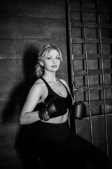 Woman hits the heavy bag with a strong kick. Concept about fit boxe, martial arts and sport. Simple woman in black boxing gloves. She is fighter for success.