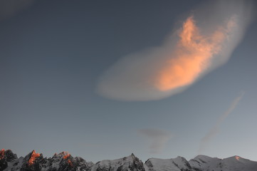 A pink cloud during sunset on dark blue sky above the mountains