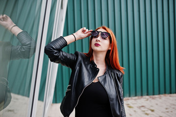 Red haired stylish girl in sunglasses wear in black, against large windows. Street fashion portrait.