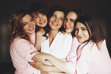 Pretty bride and laughing bridesmaids in pink robes hug each othet tender like sisters standing in the room