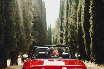Look from behind at wedding couple kissing in a red cabrio which stands between tall trees somewhere in Tuscany, Italy