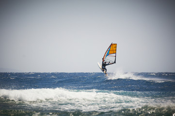 Windsurfing sail on the blue sea