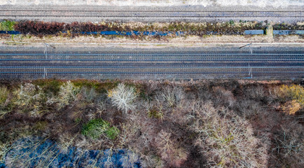 Drone view of a straight railway next to the wood