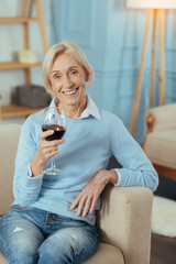Gorgeous wine. Delighted positive aged woman sitting at home and smiling while holding a glass of tasty red wine