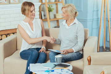 Deal. Responsible experienced young financial advisor looking happy while shaking hands with her cheerful pleasant aged client