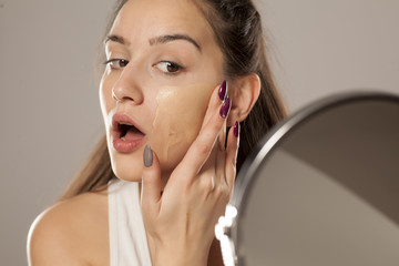 young woman applying a liquid foundation on her face with her fingers