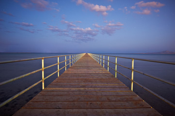 Wooden pier or jetty on sea sunset and sky reflection water