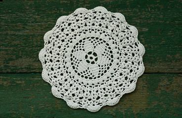 Snowflake like vintage crocheted lace napkin with wooden green background
